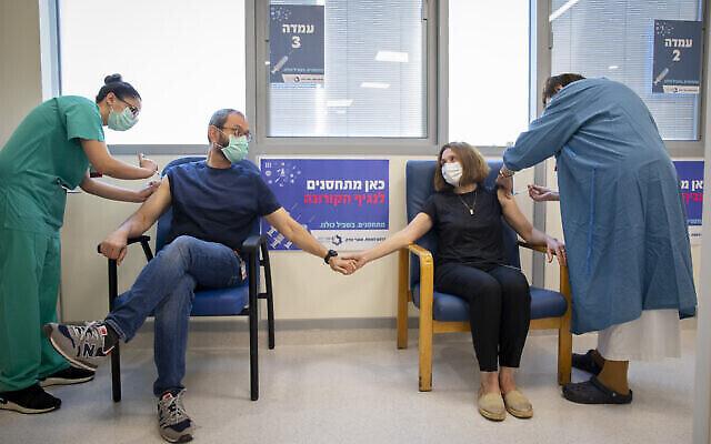 زوجان يتلقىان جرعتهما الثالثة من لقاح كوفيد-19، في مركز شعاري تسيديك الطبي في القدس، 17 أغسطس، 2021. (Olivier Fitoussi / Flash90)