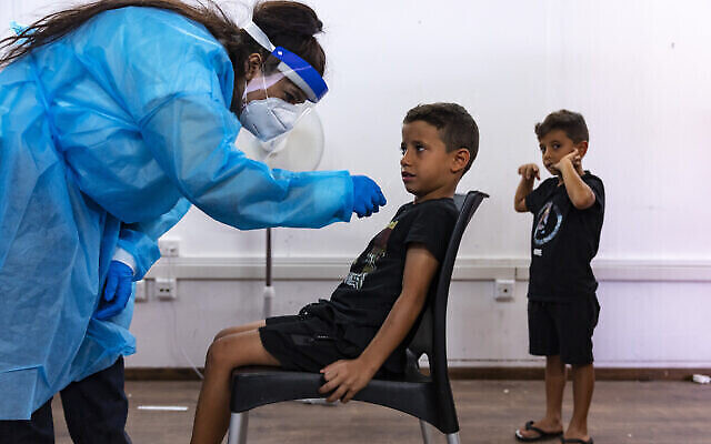 عامل طبي في نجمة داوود الحمراء يأخذ عينة من طفل في مجمع اختبار كوفيد-19 في القدس، 18 أغسطس، 2021. (Olivier Fitoussi / Flash90)