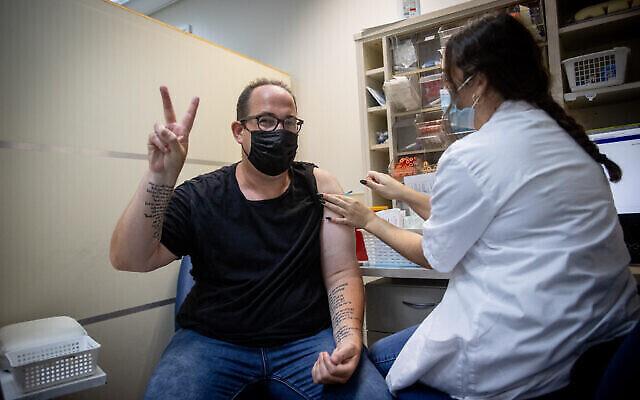 رجل إسرائيلي يتلقى جرعة ثالثة من لقاح كورونا، في مركز التطعيم التابع لخدمات الرعاية الصحية في مكابي، 22 أغسطس، 2021 (Yonatan Sindel / Flash90)