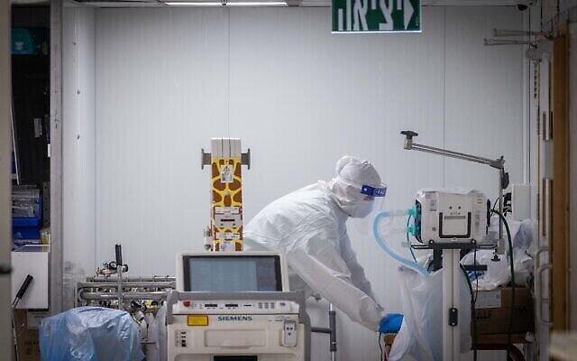 العاملون في المجال الطبي يرتدون معدات السلامة أثناء عملهم في جناح فيروس كورونا في مستشفى شعاري تسيديك في القدس، 23 أغسطس، 2021 (Yonatan Sindel / Flash90)