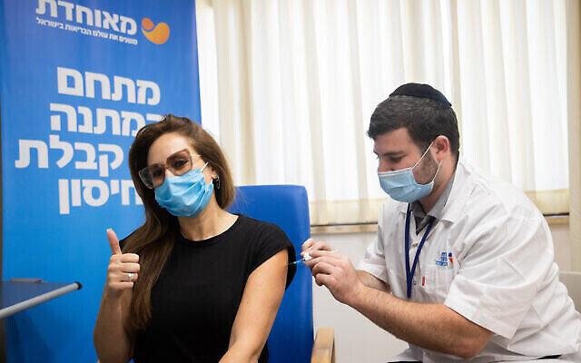 سيدة تتلقى جرعة ثالثة من لقاح كوفيد-19 في مركز تطعيم تابع لصندوق المرضى مئوحيدت في القدس، 24 أغسطس، 2021. (Yonatan Sindel / Flash90)
