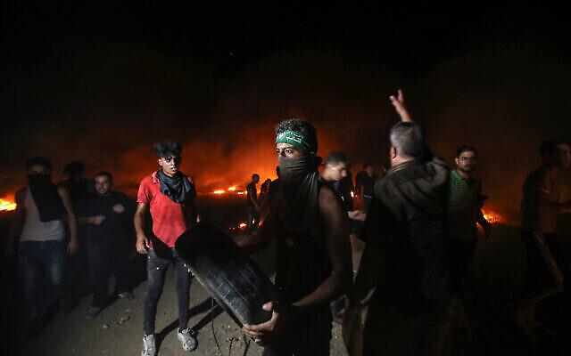 فلسطينيون يحرقون إطارات أثناء احتجاجات على طول الحدود بين قطاع غزة وإسرائيل شرقي مدينة غزة، 28 أغسطس، 2021. (Atia Mohammed / Flash90)