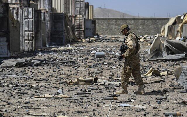 """أحد عناصر الوحدة العسكرية التابعة لطالبان """"بدري 313"""" يسير وسط حطام قاعدة وكالة المخابرات المركزية (سي آي إيه) المدمرة في منطقة ديه سابز شمال شرق كابول في 6 سبتمبر 2021 بعد أن سحبت الولايات المتحدة جميع قواتها من البلاد.( Aamir QURESHI / AFP)"""
