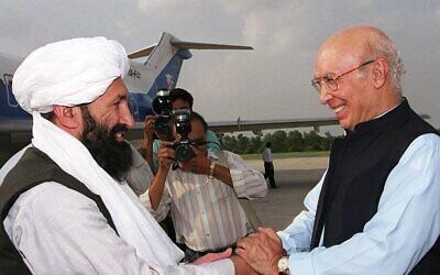 من الأرشيف: في هذه الصورة  التي التقطت في 25 أغسطس 1999 يستقبل وزير الخارجية الباكستاني سرتاج عزيز يستقبل نظيره الأفغاني من حركة طالبان الملا محمد حسن أخوند (من اليسار) في قاعدة جوية في روالبندي ، على بعد حوالي 25 كيلومترًا من إسلام أباد - أعلنت حركة طالبان الملا محمد حسن أخوند رئيسا لحكومتها الجديدة في أفغانستان في 7 سبتمبر 2021. (SAEED KHAN / AFP)