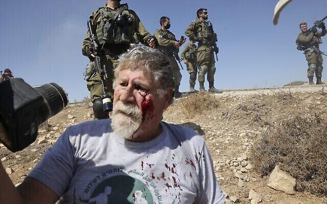 """الناشط الإسرائيلي إيلي زيف، من حركة """"مقاتلون من أجل السلام"""" ، مصاب على الأرض بعد أن دفعه جندي إسرائيلي خلال مظاهرة في المنطقة الجنوبية من مدينة الخليل بالضفة الغربية ، 17 سبتمبر، 2021. (HAZEM BADER / AFP)"""