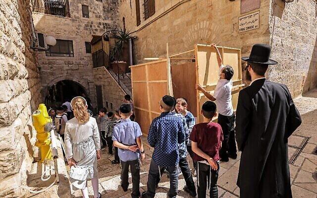 سكان يهود يقومون ببناء سوكا ، عريشة مؤقتة يتم تشييدها لاستخدامها خلال عيد السوكوت الذي يستمر لأسبوع، في البلدة القديمة في القدس، 20 سبتمبر، 2021. (Emmanuel DUNAND / AFP)