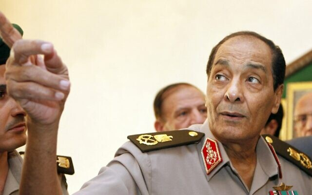 في هذه الصورة التي التقطت في 13 سبتمبر 2011، يشير المشير محمد حسين طنطاوي، رئيس المجلس العسكري الحاكم في مصر، إلى لوحة بينما كان يرافق رئيس الوزراء التركي الزائر في وزارة الدفاع في القاهرة.(Photo by AMR NABIL / POOL / AFP)