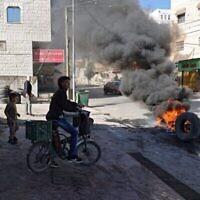 الإطارات المحترقة تغلق مدخل قرية برقين الفلسطينية، غربي جنين، في الضفة الغربية، بعد تبادل لإطلاق النار خلال مداهمة شنتها القوات الإسرائيلية، 26 سبتمبر، 2021. (Jaafar Ashtiyeh / AFP)
