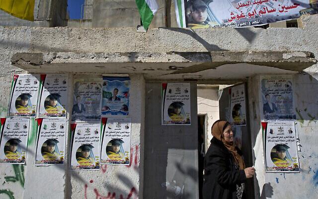 توضيحية: امرأة تنظر من مدخل منزل العائلة، حيث تم وضع ملصقات تحمل صورة حسين سالم أبو غوش (19 عاما) خلال جنازته في مخيم قلنديا للاجئين في الضفة الغربية، في ضواحي رام الله، 5 شباط، 2017. (AP/Nasser Nasser)