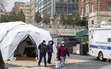 موظفو الطب الشرعي وعمال بناء في موقع مشرحة مؤقتة يجري بناؤها في نيويورك، 25 مارس، 2020. (AP Photo / Mary Altaffer / File)