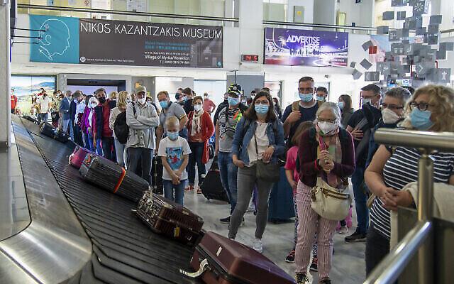 مسافرون ينتظرون وصول أمتعتهم في مطار نيكوس كازانتزاكيس الدولي في هيراكليون، في جزيرة كريت، اليونان، 14 مايو، 2021. (AP Photo / Harry Nakos ، File)