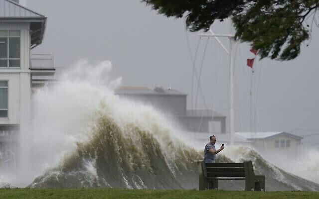 رجل يلتقط صوراً للأمواج العالية على طول شاطئ بحيرة بونتشارترين مع اقتراب إعصار أيدا،  29 أغسطس، 2021، في نيو أورلينز.  (AP Photo/Gerald Herbert)