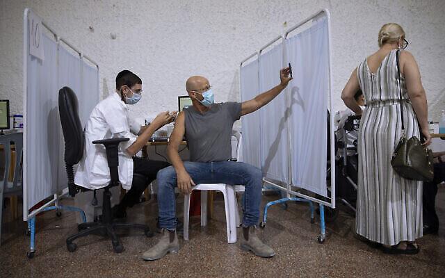 """رجل إسرائيلي يلتقط صورة """"سيلفي"""" أثناء تلقيه الجرعة الثالثة من لقاح """"فايزر-بيونتك"""" المضاد لكورونا في مركز تطعيم ضد فيروس كورونا في مدينة رمات غان الإسرائيلية، 30 أغسطس، 2021. (AP Photo / Oded Balilty)"""