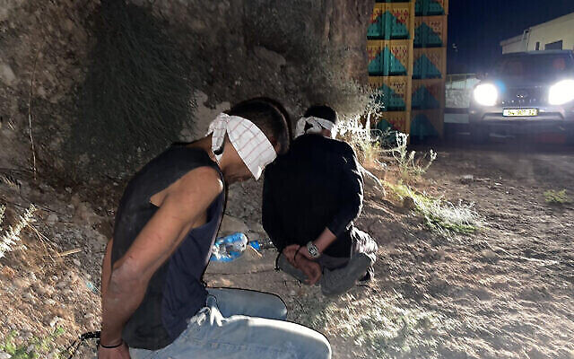 في هذه الصورة التي قدمتها الشرطة الإسرائيلية، يظهر زكريا زبيدي، من اليسار، ومحمد العارضة، وهما اثنان من بين ستة أسرى أمنيين فلسطينيين فروا من سجن جلبوع، وهما معصوبي الأعين ومكبلي الأيدي بعد أن تم القبض عليهما في بلدة أم الغنم العربية، في شمال إسرائيل، 11 سبتمبر، 2021. (Israel Police via AP)