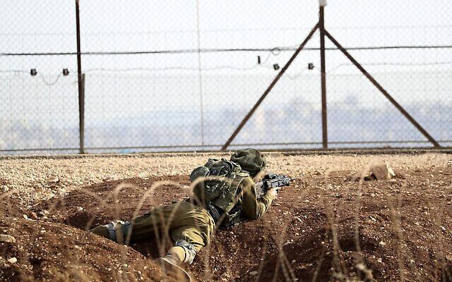 جندي إسرائيلي يتخذ موقعه على الحدود بين شمال الضفة الغربية بالقرب من جنين وإسرائيل أثناء  عمليات البحث عن فلسطينيين هربا من سجن شديد الحراسة الأسبوع الماضي، على طريق يؤدي إلى بلدة جنين بالضفة الغربية، بالقرب من غان نير الإسرائيلية، 12 سبتمبر، 2021. (AP Photo / Ariel Schalit)