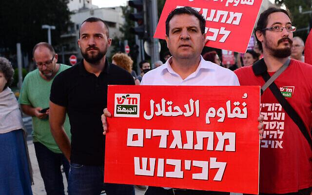 """رئيس القائمة المشتركة أيمن عودة يحمل لافتة كتب عليها """"نقاوم الاحتلال"""" خلال مظاهرة في تل أبيب، 15 مايو، 2021. (Tomer Neuberg / Flash90)"""