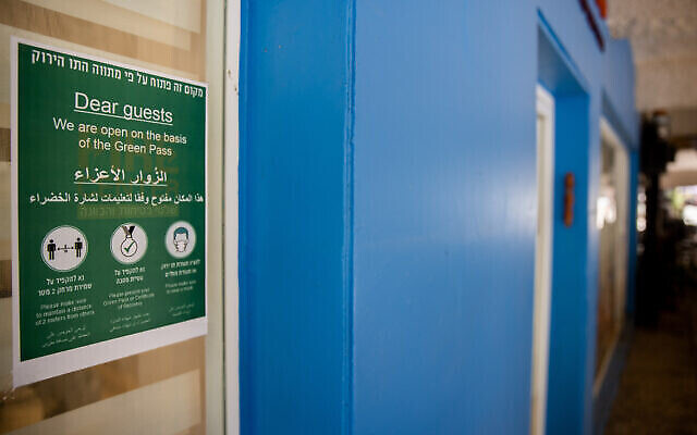 لافتة عند مدخل متجر في القدس تسمح لحاملي الجواز الأخضر فقط، واللوائح المتعلقة بالكمامات والتباعد الاجتماعي، 4 أغسطس 2021 (Yonatan Sindel / Flash90)