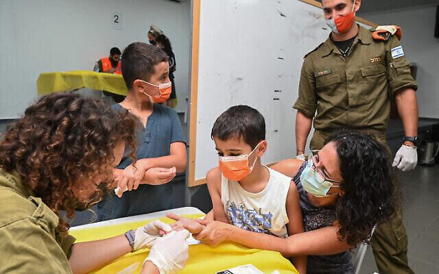 ضباط وجنود في الجيش الإسرائيلي من قيادة الجبهة الداخلية يجرون اختبارات مصلية للأجسام المضادة لدى أطفال تتراوح أعمارهم بين 3 و 12 سنة في كتسرين، في هضبة الجولان، 22 أغسطس، 2021. (Michael Giladi / Flash90)