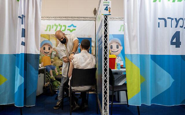 رجل يتلقى جرعته الثالثة من لقاح كورونا في مركز رعاية صحية مؤقت في القدس، 29 أغسطس 2021 (Yonatan Sindel / Flash90)