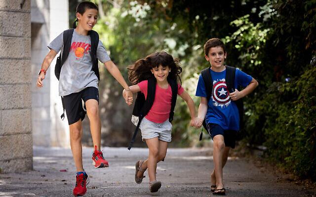 أطفال إسرائيليون يحملون الحقائب مدرسية عشية افتتاح السنة الدراسية خارج منزلهم في القدس، 31 أغسطس، 2021. (Yonatan Sindel / Flash90)