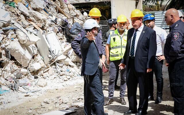 مراقب الدولة ماتنياهو إنغلمان (وسط الصورة) يزور مشهد إنهيار مبنى سكني في وسط مدينة حولون. 13 سبتمبر 2021 (Avshalom Sassoni / Flash90)
