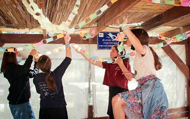 طالبات من مدرسة أوروت عتصيون يزينون سوكا (عريشة) بالقرب من غوش عتصيون في الضفة الغربية، 19 سبتمبر، 2021. (Gershon Elinson / Flash90)