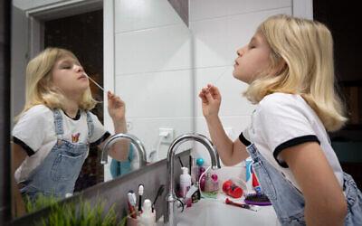 طفلة تجري اختبار مستضد منزلي سريع  لـ كوفيد-19 قبل العودة إلى المدرسة ، بعد عطلة عيد السوكوت ، في هانيئل، وسط إسرائيل، 27 سبتمبر، 2021. (Chen Leopold / Flash90)