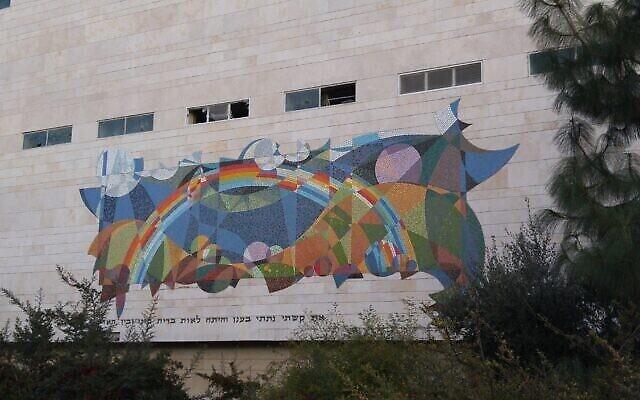 """فسيفساء """"قوس قزح"""" على مبنى هواتف بيزك في شارغ الخليل في القدس. تم نزع الفسيفساء من الجدار في تموز 2018 بسبب هدم المبنى. (رانبار / ويكيميديا)"""