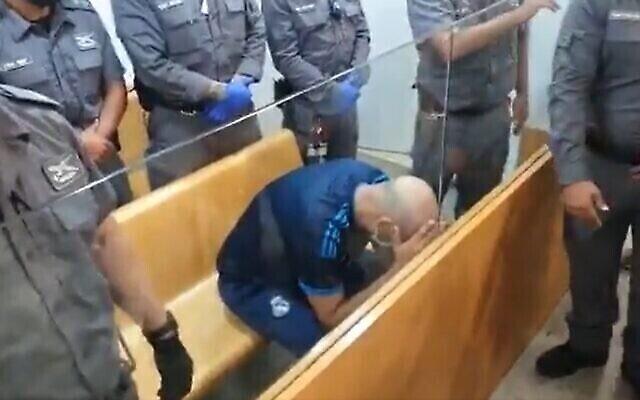 نسيم صاح، المشتبه به في جريمة دهس بسيارة في نهاريا أسفر عن مقتل متطوع من الشرطة، يغطي وجهه خلال جلسة بمحكمة الصلح في حيفا، 22 سبتمبر، 2021 (Screenshot / Twitter)