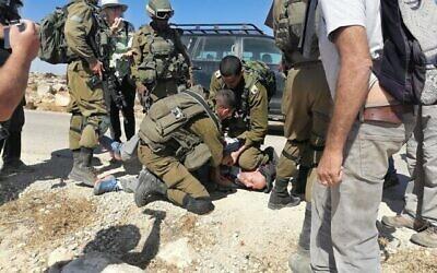 جنود إسرائيليون يعتقلون ناشط اليسار تولي فلينت بالقرب من بلدة الطواني الفلسطينة في جنوب جبل الخليل، 18 سبتمبر، 2021. (Courtesy)