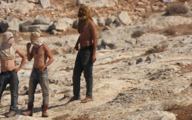 مستوطنون ملثمون بالقرب من قرية المفرقة الفلسطينية في جنوب جبال الخليل، 28 سبتمبر 2021 (Courtesy)