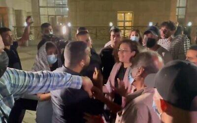 مراسل القناة 13 علي مغربي يواجه مجموعة من المتظاهرين الغاضبين أمام المحكمة المركزية في الناصرة، 11 سبتمبر، 2021. (Screenshot)