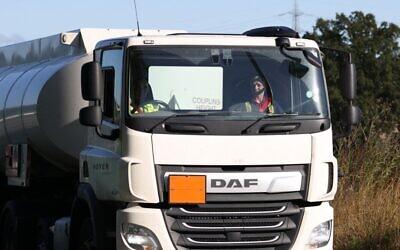 """سائق يجلس في كابينة شاحنة لنقل الوقود في """"بنسفيلد أويل ديبو"""" في هيميل هيمبستيد، شمال لندن ، في 6 أكتوبر 2021. (Adrian DENNIS / AFP)"""