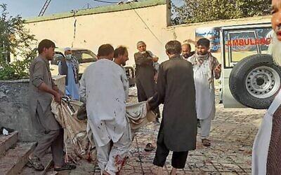 رجال أفغان ينقلون جثة ضحية إلى سيارة إسعاف بعد انفجار استهدف مسجدا في قندوز، 8 أكتوبر، 2021. (AFP)