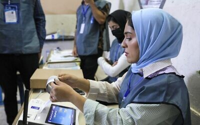 مسؤولو الانتخابات العراقيون يجرون عملية فرز الكتروني للاصوات في مركز اقتراع في اربيل، عاصمة منطقة الحكم الذاتي الكردية في شمال العراق، 10 أكتوبر، 2021. ( SAFIN HAMED / AFP)