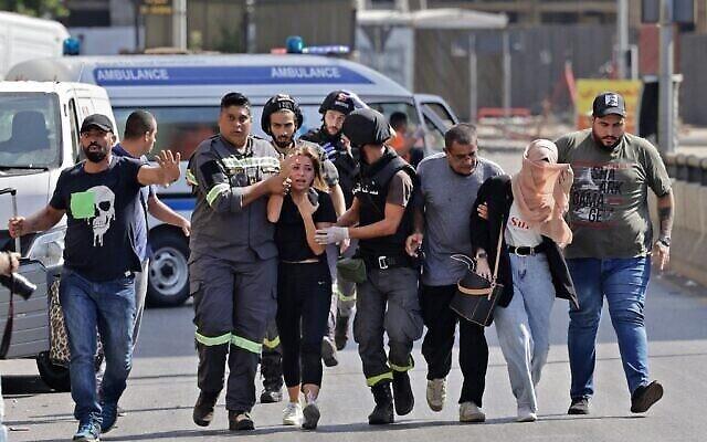 يساعد مسعفون لبنانيون في إجلاء المدنيين خلال الاشتباكات في منطقة الطيونة بالضاحية الجنوبية للعاصمة بيروت في 14 أكتوبر،  2021، إثر مظاهرة نظمها أنصار حزب الله وحركة أمل. (JOSEPH EID / AFP)