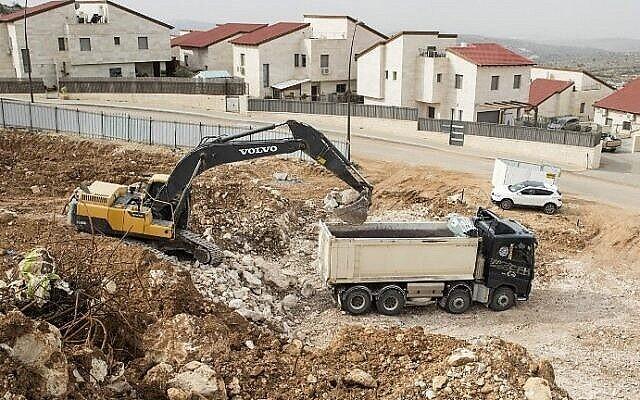 عمال فلسطينيون يعملون في موقع بناء مشروع سكني جديد في مستوطنة أريئل الاسرائيلية بالقرب من مدينة نابلس في الضفة الغربية، 25 يناير، 2017. (AFP Photo / Jack Guez)