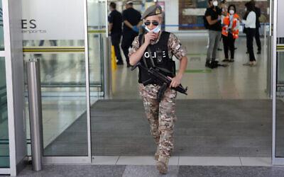 توضيحية: شرطية تعدل قناعها أثناء حراستها في مطار لارنكا الرئيسي في قبرص، يوم الثلاثاء، 9 يونيو، 2020 (AP Photo / Petros Karadjias)