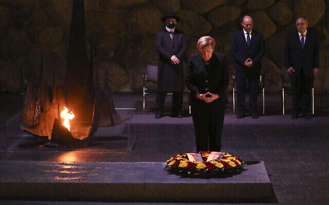 """المستشارة الألمانية أنغيلا ميركل تضع إكليلا من الزهور في """"قاعة الذكرى""""، يقف وراءها رئيس الوزراء نفتالي بينيت، الثاني على اليمين، خلال زيارة لمتحف """"ياد فاشيم"""" لتخليد ذكرى ضحايا المحرقة في القدس، 10 أكتوبر، 2021. (AP Photo / Ariel Schalit)"""