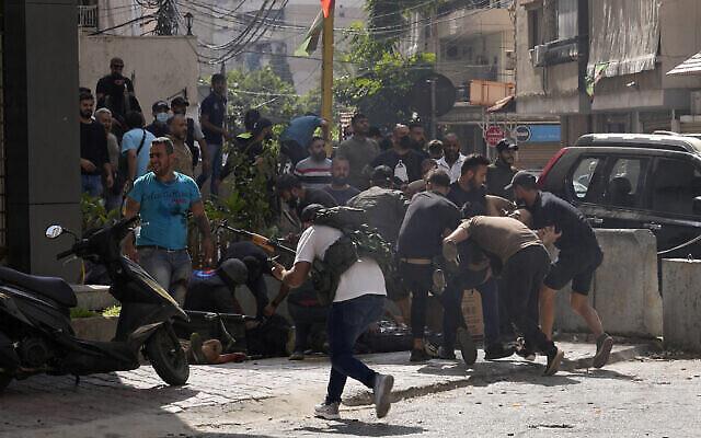 أنصار جماعة شيعية متحالفة مع حزب الله يساعدون رفيقهم الذي أصيب خلال اشتباكات مسلحة اندلعت خلال مظاهرة في الضاحية بجنوب بيروت، لبنان، 14 أكتوبر، 2021. (AP Photo / Hassan Ammar)