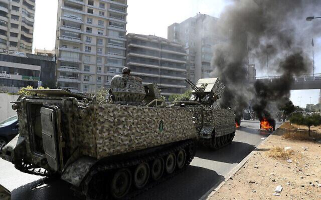 جنود من الجيش اللبناني يحرسون عربتهم المصفحة بينما يحرق أنصار حزب الله وحركة أمل الشيعية حاويات القمامة لإغلاق طريق خلال مظاهرة في بيروت، لبنان، في 14 أكتوبر 2021 (AP Photo / Bilal Hussein)