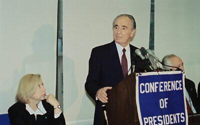 القنصل العام آنذاك في نيويورك كوليت أفيتال تنظر إلى وزير الخارجية آنذاك شيمون بيرس يخاطب مؤتمر رؤساء المنظمات اليهودية الكبرى، 23 مايو 1994، في نيويورك. (صورة أسوشيتد برس / ديفيد كارب)