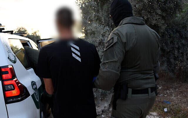 في هذه الصورة المنشورة من 24 سبتمبر 2021، يسير شرطي مع مشتبه به تم اعتقاله في سلسلة مداهمات ضد عناصر الجريمة المنظمة في بلدات عربية ودرزية في شمال إسرائيل.(Israel Police)