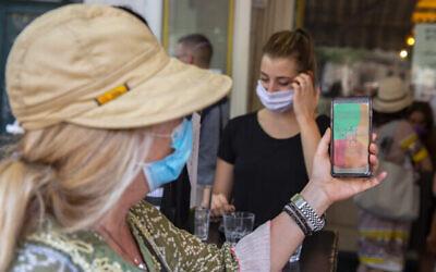 أشخاص يقدمون شهادات تطعيم عند مدخل مخبز في القدس، 8 أغسطس، 2021. (Olivier Fitoussi / Flash90)