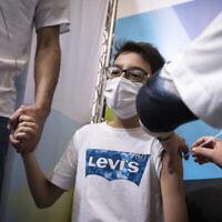 """طفل إسرائيل يتلقى جرعته من من لقاح كوفيد-19 في صندوق المرضى """"كلاليت""""،  9 سبتمبر، 2021، في القدس. (Olivier Fitoussi / Flash90)"""