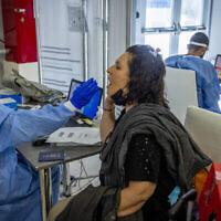 عاملة رعاية صحية تأخذ عينة من امرأة لفحص فيروس كورونا، بعد عودتها من الخارج في مطار بن غوريون الدولي في 20 سبتمبر 2021 (Nati Shohat / Flash90)