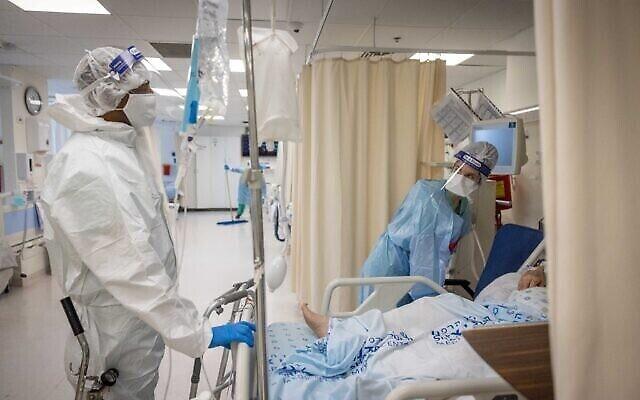 أعضاء طاقم طبي يرتدون زيا واقيا أثناء عملهم في قسم كورونا في مستشفى شعاري تسيديك في القدس، 23 سبتمبر، 2021. (Yonatan Sindel / Flash90)