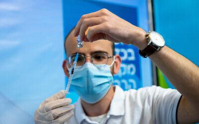 عامل طبي يحضر جرعة من لقاح كوفيد-19 في القدس، 7 أكتوبر، 2021. (Olivier Fitoussi / Flash90)