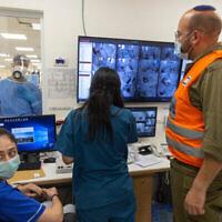 تجمع طاقم مستشفى شعاري تسيديك وجندي من الجيش الإسرائيلي حول شاشات الكمبيوتر، 14 أكتوبر، 2021 (Olivier Fitoussi / Flash90)