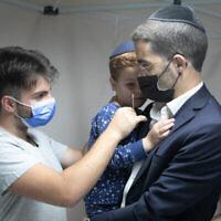 رجل حريدي يجري لابنه فحص كوفيد-19 في اللد، 17 أكتوبر، 2021. (Yossi Aloni / Flash90)